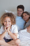 Portrait of a boy sitting on his parents's bed. While looking at the camera Stock Photos