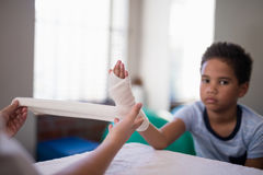 Portrait of boy sitting at table while female therapist wrapping bandage on hand. In hospital ward Stock Images