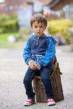 Portrait of a boy, sitting on a tree trunk Royalty Free Stock Image