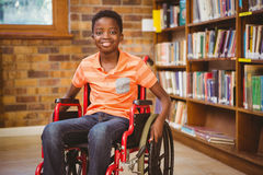 Portrait of boy sitting in wheelchair at library. Portrait of little boy sitting in wheelchair at the library Royalty Free Stock Image