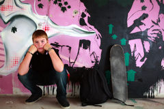 Portrait of a Boy with skateboard. Teenage boy with skateboard against purple graffity wall check out more of the same series Stock Images