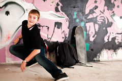 Portrait of a Boy with skateboard. Teenage boy with skateboard against purple graffity wall check out more of the same series Stock Photography