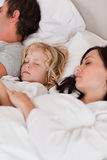 Portrait of a boy sleeping between his parents. In a bedroom Royalty Free Stock Photo