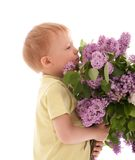 Portrait of boy smelling bouquet of lilac Stock Image