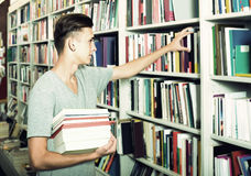 Portrait of  boy standing among bookshelves and searching for bo Stock Photography