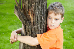 Portrait of boy, that stands hugging tree Stock Photography