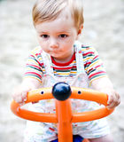 A portrait of a   boy on a swing in a playground. Stock Images