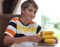Portrait of a boy at a table with a bowl of corn Royalty Free Stock Image
