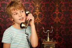 Portrait of boy talking to an old phone Royalty Free Stock Photo