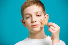 Portrait of a boy tearing off adhesive plaster from his che Stock Photos