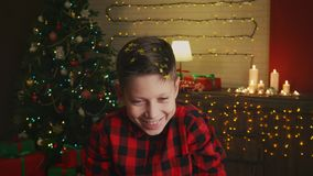 Portrait of a boy throwing confetti in a room with Christmas decoration. Stock footage stock video footage