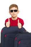 Portrait of boy with travel bags wearing sunglasses showing thumbs Stock Images