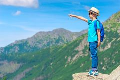 Portrait of a boy traveler standing on a rock and pointing. At a mountain Stock Photos