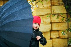 Portrait of a boy with an umbrella on a spring walk. Portrait of a little boy with an umbrella on a spring walk royalty free stock image