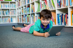 Portrait of boy using digital tablet in school library Royalty Free Stock Photography