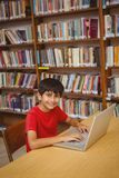 Portrait of boy using laptop in library Stock Photo