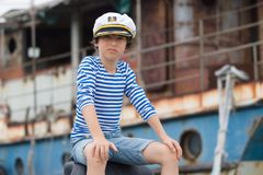 Portrait of a boy in a vest Telnyashka. And captain`s cap royalty free stock images