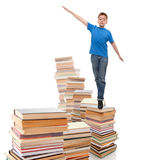 Stepping Up To School Work. Portrait of boy walking from top to top of book piles Royalty Free Stock Photography