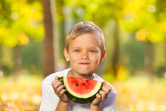Portrait of boy with watermelon sitting in forest Stock Images