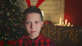 Portrait of a boy wearing Christmas reindeer antlers stock footage