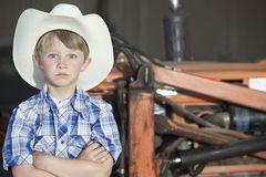 Portrait of a boy wearing cowboy hat while standing with arms crossed against machine Royalty Free Stock Images