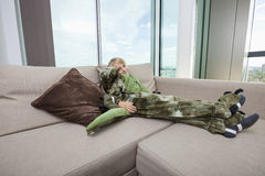 Portrait of boy wearing dinosaur costume relaxing on sofa at home Stock Images