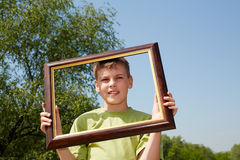 Portrait of boy, who holds picture frame Stock Photos