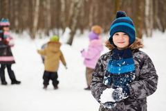 Portrait of boy who stands in winter park and holds snowball Royalty Free Stock Image