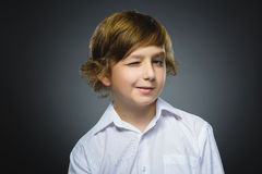 Portrait of boy winking over gray background. Positive human emotion facial expression body language royalty free stock photography