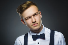 Portrait of boy winking over gray background. Positive human emotion facial expression body language Stock Images