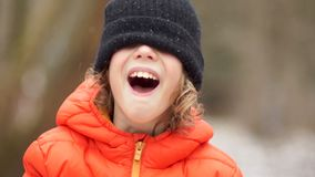 Portrait of a boy in a winter knitted cap. His eyes are closed with a hat, he laughs stock video footage