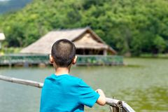 Portrait of a boy and The wooden raft in the water reservoirs. royalty free stock photos