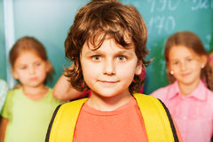 Portrait of boy with yellow bag near chalkboard Royalty Free Stock Photography