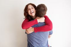 Boyfriend and girlfriend hugging each other against white background. Portrait of boyfriend and girlfriend hugging each other against white background stock image