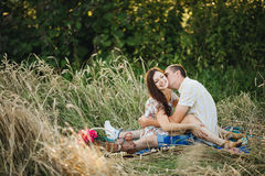 Portrait of  boyfriend and girlfriend sitting among grass in meadow smiling and looking at camera. Picnic in sunny summer day outd Stock Image
