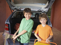 Portrait Of Boys Carrying Suitcases Against Car. Portrait of two smiling boys carrying suitcases in front of car Stock Photo