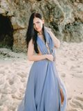 Portrait of bride in blue wedding dress at beach with sunset or sunrise colors. Wedding style. Portrait of bride in blue wedding dress at beach with sunset or Royalty Free Stock Images