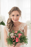 Portrait of a bride with a bouquet of flowers. Young beautiful bride in a white wedding dress holding a bouquet of roses flowers Stock Photography