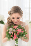 Portrait of a bride with a bouquet of flowers. Young beautiful bride in a white wedding dress holding a bouquet of roses flowers Royalty Free Stock Image