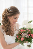 Portrait of a bride with a bouquet of flowers. Young beautiful bride in a white wedding dress holding a bouquet of roses flowers Stock Photo