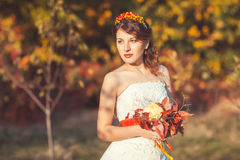 Portrait of bride with bouquet in park. Portrait of the beautiful bride with a bouquet in the autumn park Royalty Free Stock Image
