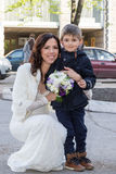 Portrait of bride with a child. Portrait of a beautiful bride with a bouquet and a little boy standing next Stock Images