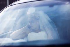 Portrait bride through glass of car Stock Image