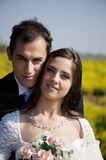 Portrait of a bride with groom. Portrait of a young woman and a young man standing in a flower field Royalty Free Stock Photos