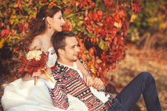 Portrait of bride and groom in autumn park. They sit on the grass in autumn park, bride groom hugging Royalty Free Stock Photo