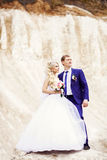 Portrait of the bride and groom on the background of white cliff Royalty Free Stock Images