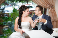 Portrait of bride and groom drinking champagne at luxury restaurant Royalty Free Stock Photography
