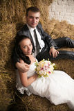 Portrait of bride and groom hugging on hay at stable Stock Photography