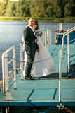 Portrait of bride and groom hugging on pier on river Stock Photography