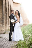 Portrait of bride and groom hugging under tall brick castle walls Stock Photography